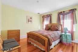 spacious bedroom, two windows, hardwood floor, closet