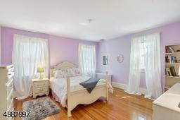 spacious bedroom, three windows, hardwood floor, closet