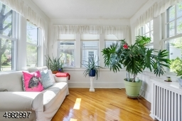 sun-lit, wall of windows sun room, wood floors