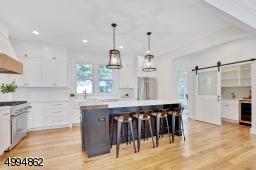 Chefs kitchen features an 8ft center island, 36in Thermador range, SS appliances, quartz countertops, double farm sink, custom range hood, custom butcherblock, drawer organizers, walk-in pantry with barn door, bar sink and wine fridge