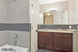 Double vanity, tub/shower with custom tiles and linen closet.