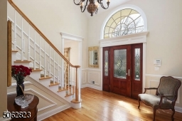Two-story foyer with hardwood flooring.