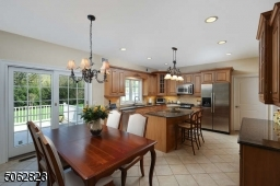 Kitchen with stainless steel appliances, center island breakfast bar and outside access.