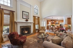 Open to kitchen with fireplace and hardwood flooring.