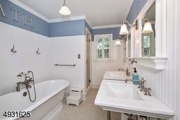 Configured from combining 2 bathrooms, this bathroom has a soaking tub, stall shower, private toilet room, twin console Kohler sinks, built-in cabinetry and shutters for privacy.