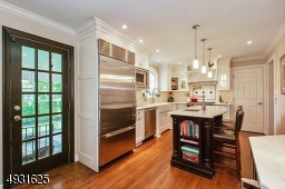 High end custom inset cabinetry, Sub Zero refrigerator & Viking appliances, center island with prep sink, and white carrera marble countertops.