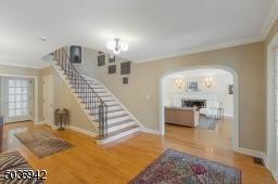 Wood floors & elegant staircase with metal railing & balusters