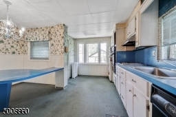 Large eat in kitchen with many windows and access to the screened in porch.