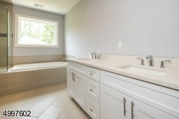Dual sinks and contains an extra door for added privacy.