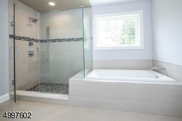 Offers a fantastic frameless glass shower and separate tub for your bathing enjoyment.