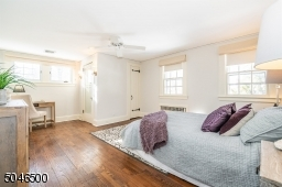 Spacious and freshly painted bedroom with ceiling fan, sconce lighting, desk area, 2 closets and full white bath with stall shower and large pedestal sink