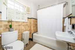 Well maintained hall bathroom with vintage tile and shower over bathtub
