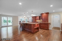 Huge center island with granite counter top. Kitchen has an abundance of cabinets.