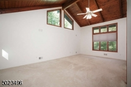 Comfortable room with high ceilings, a ceiling fan, double closets and windows on three walls.