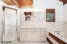 Vaulted ceiling, Jetted tub, stall shower, and large vanity w/Corian countertop.