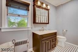 Newly renovated black and white tiled bathroom with tub/shower.