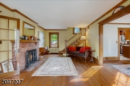 Ground floor living room with wood molding, hardwood flooring and fireplace