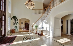 Sun drenched gracious Foyer with two story Mahogany door.