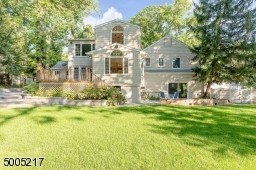 Spectacular backyard oasis with 2 patios, wrap around deck, fenced-in yard, wooded borders