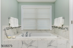 Luxurious master bath with soaking tub, stall shower with frameless glass door, double sink vanity & tile floor