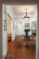 with expansive crown moldings, wainscot panels and beautiful chandeliers