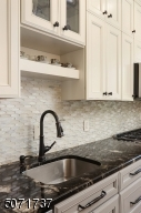 gourmet eat-in kitchen with custom cabinetry, touch-less faucet, stone mosaic backsplash