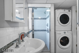 This bathroom is located off the family room. The stackable washer/dryer are included.