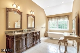 Master bath with custom cabinetry, heated flooring and a soaking tub and a stall shower.