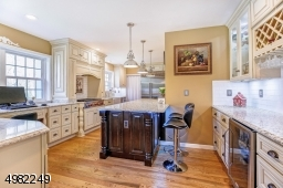 Renovated kitchen with stainless steel appliances, custom cabinetry and two breakfast bars make for easy food prep and informal dining.