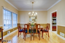 Dining Room is formal featuring custom moldings including ceiling molding, chair rail and medallion.
