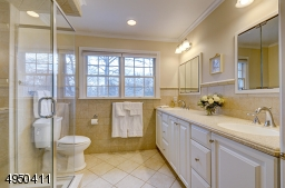Features double sinks with Corian counter top and ovesized glass-enclosed shower with built-in bench and niche.