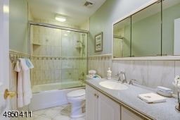So pretty! - Porcelain floor, tiled glass enclosed shower-over-tub and custom wood vanity with Corian counter top.