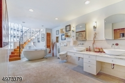 Beautiful master bath with double vanities, a luxury spa tub and over-sized walk-in shower.  There is a spiral staircase that leads up into the Silo!