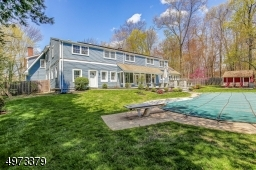 Enjoy the blue stone patio overlooking the in-ground pool on this expansive park-like property.