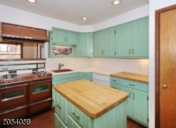 Charming kitchen with new laminated floor.. Vintage stove with double ovens & broilers. Under the cabinet lighting and plenty of cabinet space.