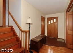 Entry hall with hardwood floor and guest closet.