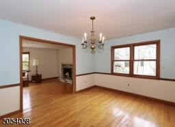 Formal dining room with chair rail and gleaming hardwood floors.