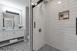 Larger vanity, full tiled shower with glass doors.