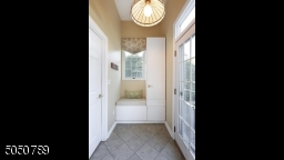 Mud room with built-in cabinetry & window seat offers plenty of storage and a place to hang your coats, backpacks, etc.