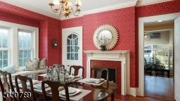 Decorative fireplace with glazed tiles & handsome mantle, built-in china cabinet, crown molding & butlers door to kitchen