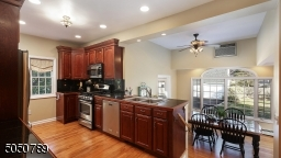 Meal prep made easy in this working kitchen with gorgeous granite counters & backsplash, undermount cabinet lighting, pantry closet and double stainless steel sink overlooking Breakfast Room,