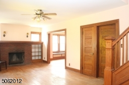 LR spans entire front of this home -- 24 ft across; hardwood floor; FPL (as is) is flanked by glass-doored built-ins and wall sconces
