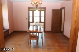 Generously-sized Dining Room; features hardwood floor, chandelier, large window w/ window seat