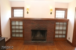 Close-up view of FPL, glass-doored built-ins, vintage windows, pair of wall sconces
