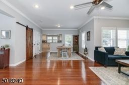 Hardwood floors, crown molding and barn door to closet