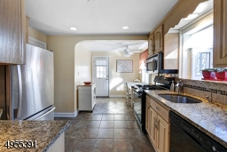 Kitchen with granite counters, tile floor and backsplash, dishwasher, gas stove, stainless steel sink and refrigerator, greenhouse window, eating area and door to deck.