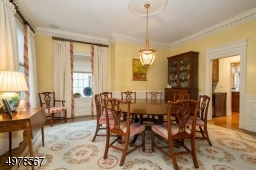 This view is from the French doors in the foyer looking into the large square room.  Seller has chosen a round table, perfect for dinner parties.