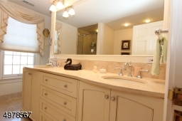 Tall twin sinks with marble vanity make getting ready easy.  Soothing cream and white colors enhance the spa feel.  Out of sight is a soaking tub and large tile shower stall.