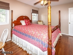 Inviting guest room with two sun filled windows and paddle fan