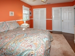Charming bedroom with double closets, hardwood floor and paddle fan